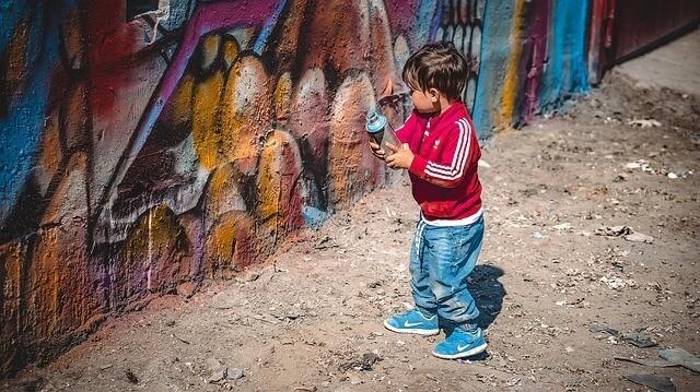 kid holding a paint spray can