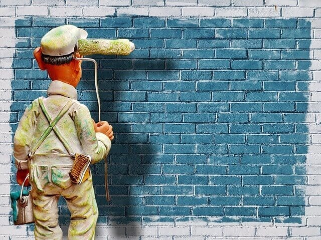 painter on a brick wall